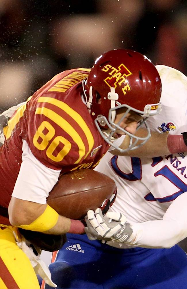 Iowa State wide receiver Justin Coleman (80) tries to fight off a tackle by Kansas linebacker Jake Love after catching a pass during the first half of an NCAA college football game in Ames, Iowa, Saturday Nov. 23, 2013