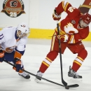 New York Islanders' Lubomir Visnovsky, left, from Slovakia, steals the puck from Calgary Flames' Paul Byron during the first period of an NHL hockey game Friday, March 7, 2014, in Calgary, Alberta The Associated Press