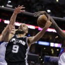 San Antonio Spurs' Tony Parker, center, of France, is defended by Los Angeles Clippers' Blake Griffin, left, and Darren Collison during the first half of an NBA basketball game on Monday, Dec. 16, 2013, in Los Angeles. (AP Photo/Jae C. Hong)