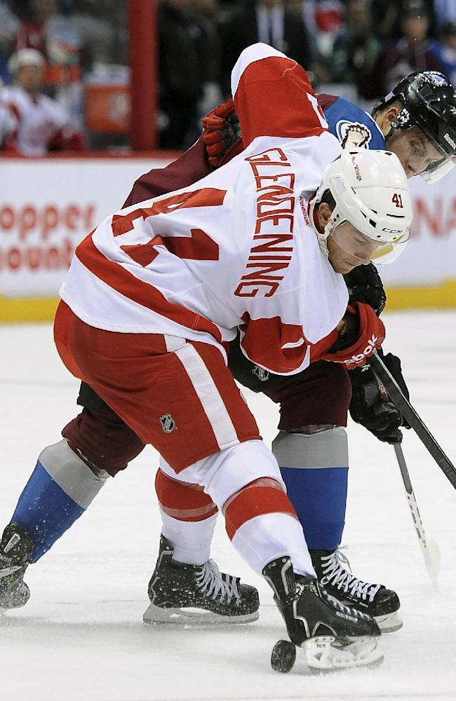 Detroit Red Wings right wing Luke Glendening, front, and Colorado Avalanche center John Mitchell, rear, compete for the puck in the second period of an NHL hockey game Thursday, Oct. 17, 2013, in Denver