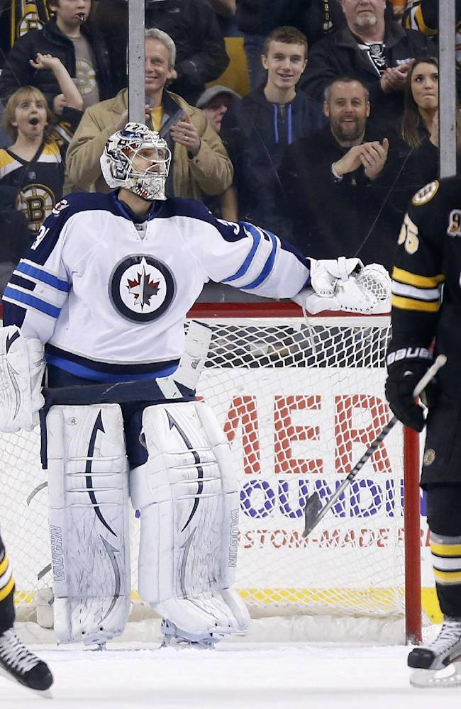 Winnipeg Jets' Ondrej Pavelec, center, stands in the goal as Boston Bruins' Johnny Boychuk (55) and Torey Krug (47) celebrate a goal by teammate Reilly Smith, left, in the third period of an NHL hockey game in Boston, Saturday, Jan. 4, 2014. The Bruins won 4-1