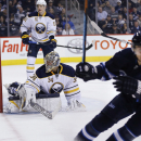 Winnipeg Jets' Michael Frolik (67) turns away after scoring on Buffalo Sabres goaltender Michal Neuvirth (34) as Sabres' Nikita Zadorov (51) watches during the second period of an NHL hockey game Tuesday, Dec. 16, 2014, in Winnipeg, Manitoba The Associate