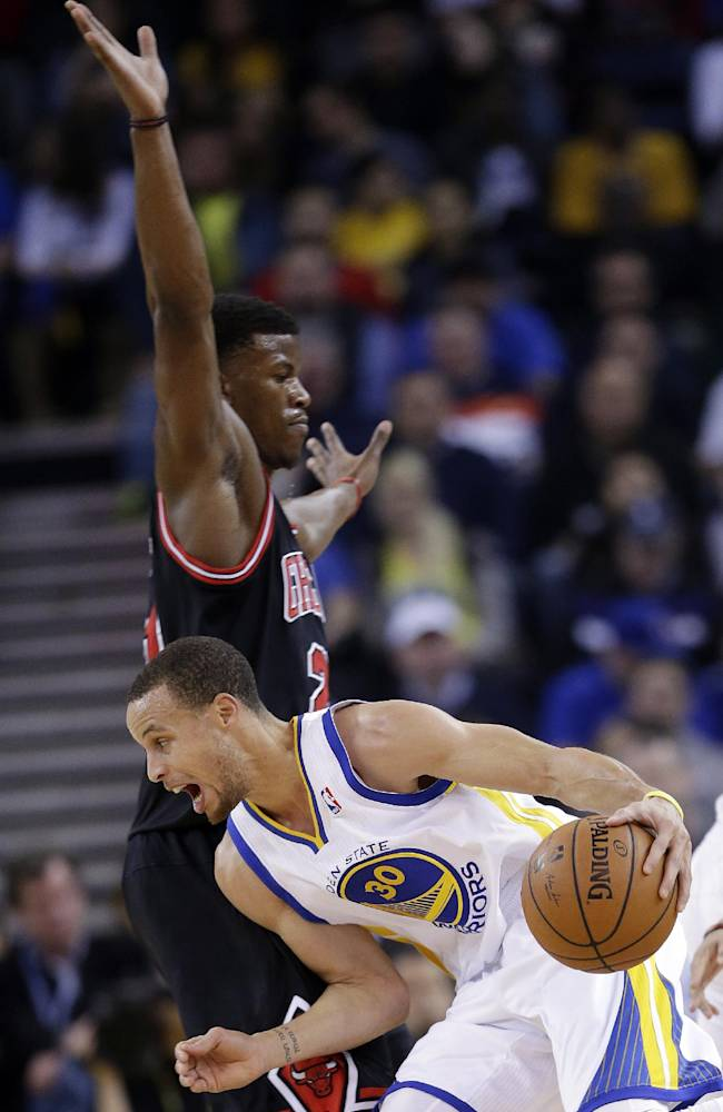 Golden State Warriors' Stephen Curry (30) dribbles around Chicago Bulls' Jimmy Butler during the first half of an NBA basketball game, Thursday, Feb. 6, 2014, in Oakland, Calif