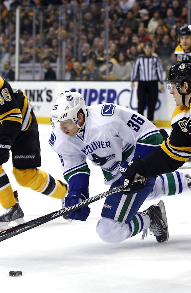 Vancouver Canucks right wing Jannik Hansen (36) chases the puck against Boston Bruins center David Krejci (46), defenseman Torey Krug (47) and right wing Jarome Iginla (12) during the first period of an NHL hockey game in Boston on Tuesday, Feb. 4, 2014