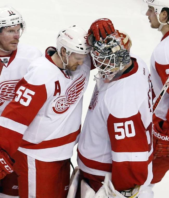 Detroit Red Wings players, including Daniel Alfredsson (11), Niklas Kronwall (55), Brendan Smith (2) and Xavier Ouellet (61) gather around goalie Jonas Gustavsson (50) after losing 4-2 to the Boston Bruins in Game 5 in the first round of the NHL hockey Stanley Cup playoffs  in Boston, Saturday, April 26, 2014. The loss eliminated the Red Wings from the playoffs