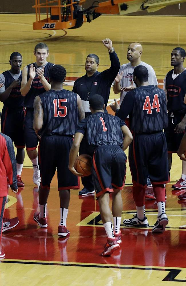 Rutgers men's basketball head coach Eddie Jordan, center, holds up his hand to call his players in during practice in Piscataway, N.J., Tuesday, Oct. 22, 2013. Jordan was named head coach last April, as the school sought to move forward from a scandal that forced the firing of coach Mike Rice and the resignation of athletic director Tim Pernetti. Jordan played for the Scarlet Knights from 1973-77 and was a member of Rutgers' Final Four team in 1976