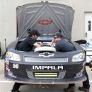Crew members for Nationwide Series driver T.J. Bell chat as they work on the engine of the car before the start NASCAR Nationwide Series practice for the Indiana 250 auto race at the Indianapolis Motor Speedway in Indianapolis, Thursday, July 26, 2012. (AP Photo/AJ Mast)