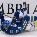Vancouver Canucks left wing Mike Zalewski (40) and San Jose Sharks defenseman Brent Burns crash into the boards as they fight for the puck during the second period of an NHL preseason hockey game in Vancouver, British Columbia, Tuesday, Sept. 23, 2014. Th
