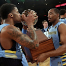 Marquette guard Vander Blue, left, who scored the winning basket, kisses the Big East Conference regular season Championship trophy, after defeating St. John's 60-67 in overtime in an NCAA college basketball game in New York's Madison Square Garden, Saturday, March 9, 2013. Teammate Derrick Wilson holds the trophy. (AP Photo/Richard Drew)
