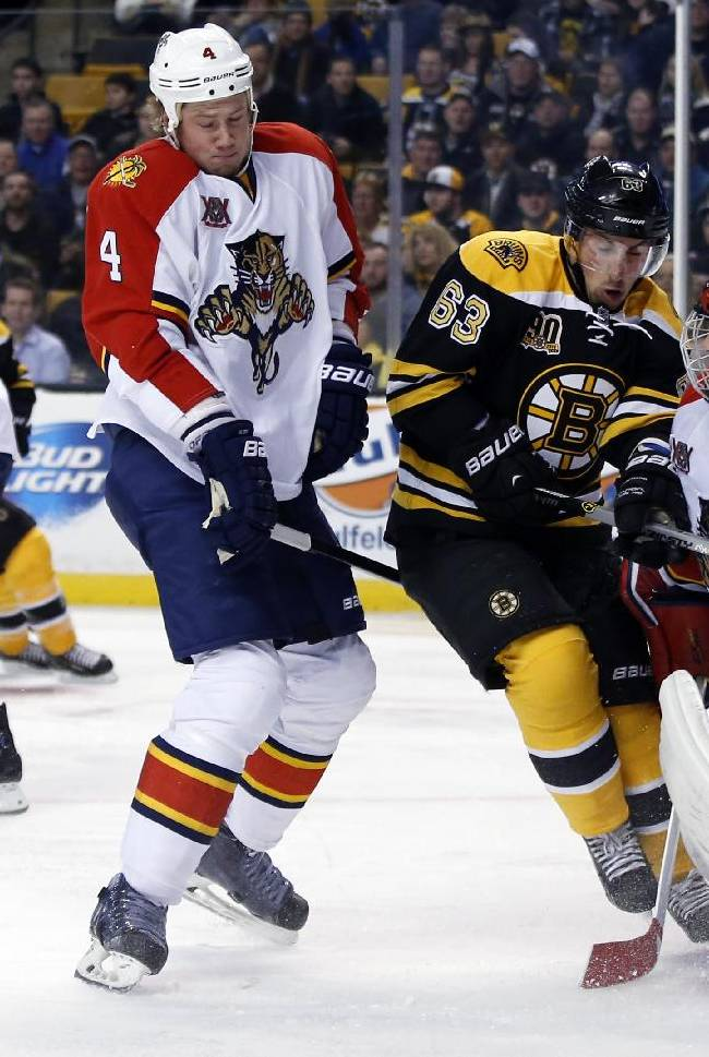 Boston Bruins left wing Brad Marchand (63) fights for position against Florida Panthers defenseman Dylan Olsen (4) and goalie Tim Thomas (34) as the puck squirts away during the second period of an NHL hockey game in Boston, Tuesday, March 4, 2014