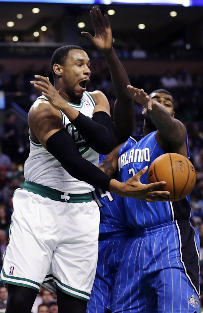 Boston Celtics power forward Jared Sullinger (7) passes the ball as he is pressured by Orlando Magic power forward Kyle O'Quinn, right, during the first quarter of an NBA basketball game, in Boston, Monday, Nov. 11, 2013