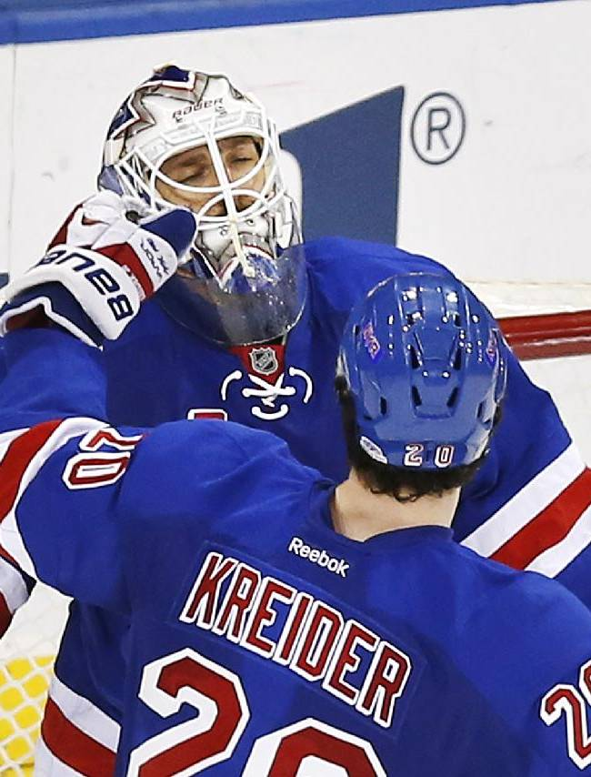 New York Rangers goalie Henrik Lundqvist, of Sweden, celebrates as teammate Chris Kreider (20) skates up to congratulate him after Lundqvist made the game-winning save against the Calgary Flames during the shootout portion of an NHL hockey game Sunday, Dec. 15, 2013, in New York. The Rangers won 4-3 in a shootout