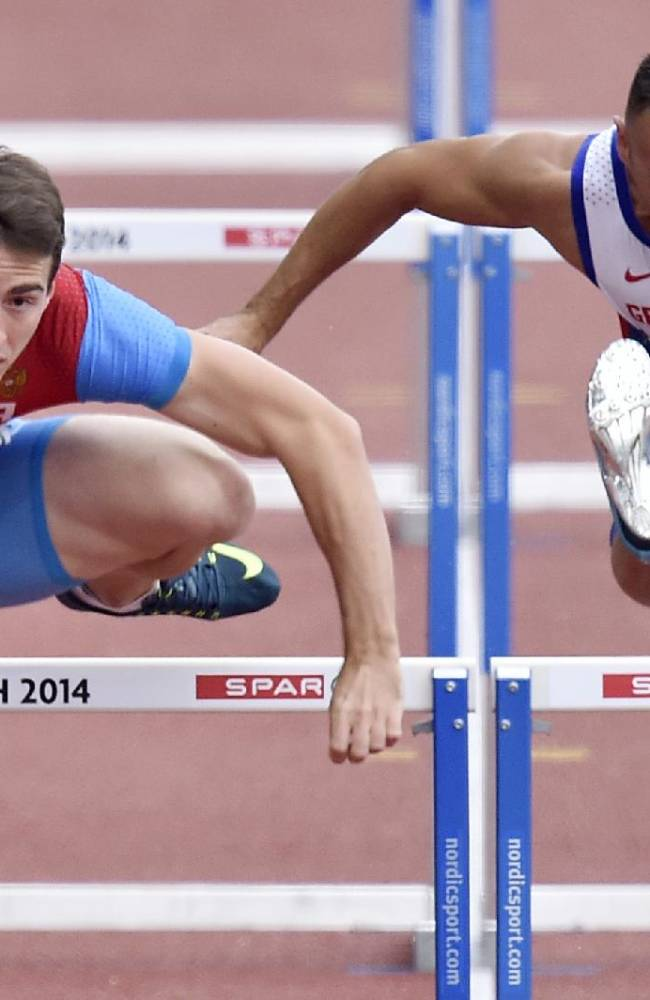 Russia's Sergey Shubenkov, left, and Britain's Andy Turner compete in a men's 110m hurdles first found heat during the European Athletics Championships in Zurich, Switzerland, Wednesday, Aug. 13, 2014