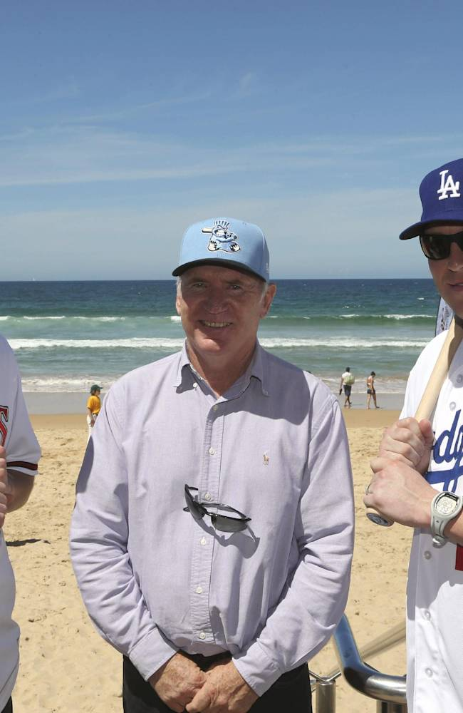 Major League baseball players Los Angeles Dodgers catcher A.J. Ellis and Arizona Diamondbacks pitcher Patrick Corbin pose with former Australian cricket captain Allan Border for photographers during a visit to Manly Beach in Sydney Wednesday, Nov. 20, 2013. The Dodgers and the Diamondbacks will play in their two-game series in Australia that opens next year's Major League Baseball season