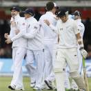 England's James Anderson, left, and Graeme Swann embrace after New Zealand are all out for 207 as New Zealand's Trent Boult passes, right, during their first test match against New Zealand at Lord's cricket ground in London, Saturday, May 18, 2013. (AP Photo/Kirsty Wigglesworth)