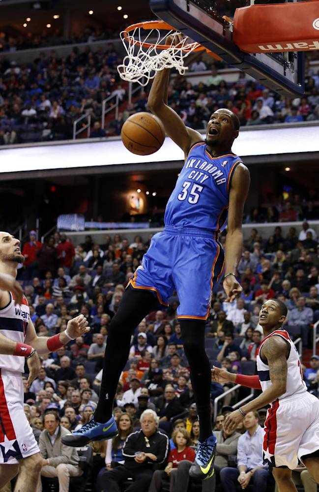 Oklahoma City Thunder forward Kevin Durant (35) dunks as Washington Wizards center Marcin Gortat, left, from Poland, and guard Bradley Beal, right, watch in the first half of an NBA basketball game on Saturday, Feb. 1, 2014, in Washington