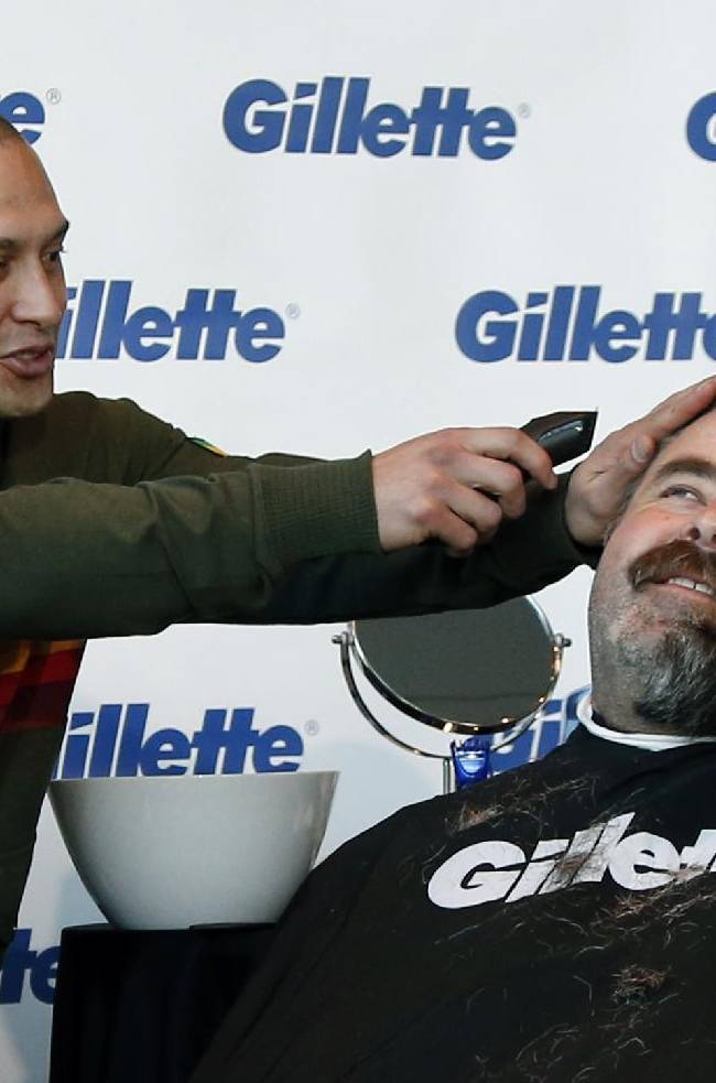 Boston Red Sox player Shane Victorino, center, kids around with a razor as Boston Police Officer Steve Horgan, right, is shaved for One Fund Boston, the Boston Marathon charity for bombing victims, during a shave-off in Boston, Monday, Nov. 4, 2013. Horgan, who was stationed in the Boston Red Sox bullpen at Fenway Park, became a city icon after he was photographed with his arms in the air celebrating Red Sox's David Ortiz's grand slam in the AL championship baseball series against Detroit
