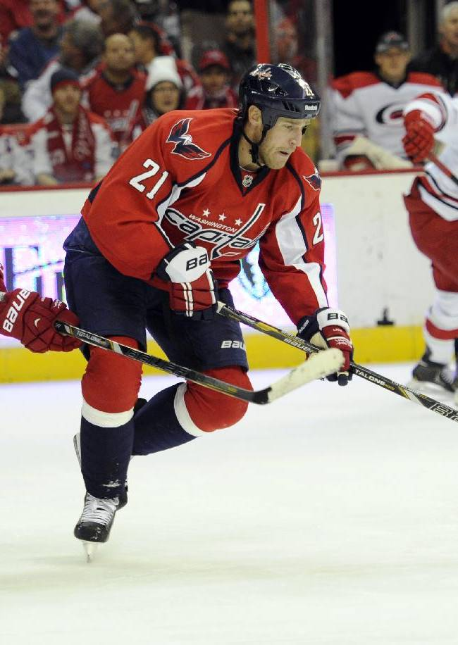 Washington Capitals center Brooks Laich (21) skates with the puck against Carolina Hurricanes right wing Alexander Semin (28), of Russia, during the second period of an NHL hockey game, Thursday, Jan. 2, 2014, in Washington
