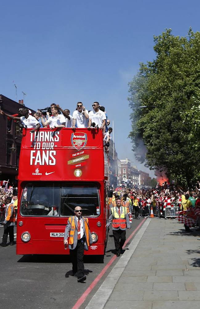 Arsenal's soccer team players parade through the street of London Sunday, May 18, 2014, aboard an open top bus in celebration of their English FA Cup win. Aaron Ramsey scored in extra time to clinch a 3-2 victory over Hull on Saturday, making Arsenal FA Cup Winners for the fifth time in Arsene Wenger's 14-year  tenure as coach of The Gunners