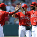 Los Angeles Angels' Raul Ibanez, center, Yoslan Herrera, left, and Ian Stewart celebrate their 14-2 win over the New York Mets after the ninth inning of a baseball game in Anaheim, Calif., Sunday, April 13, 2014 The Associated Press