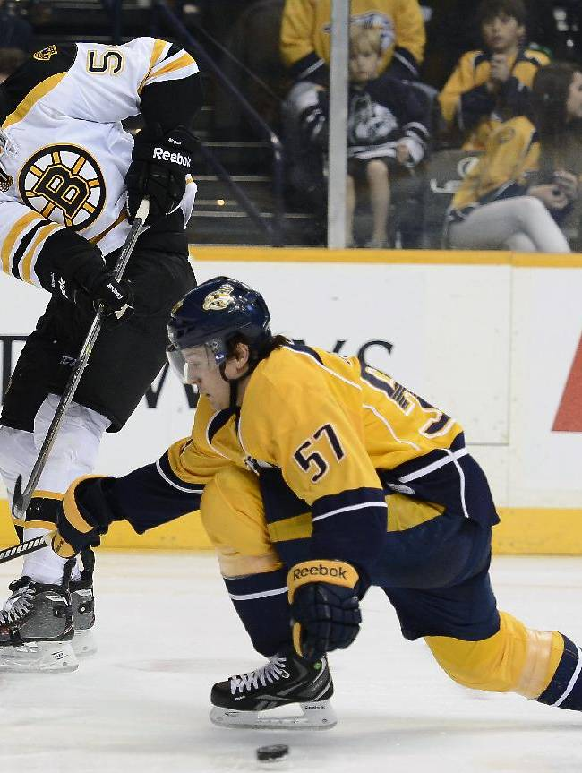 Boston Bruins defenseman Adam McQuaid (54) passes the puck by Nashville Predators forward Gabriel Bourque (57) in the third period of an NHL hockey game on Monday, Dec. 23, 2013, in Nashville, Tenn. The Bruins won 6-2