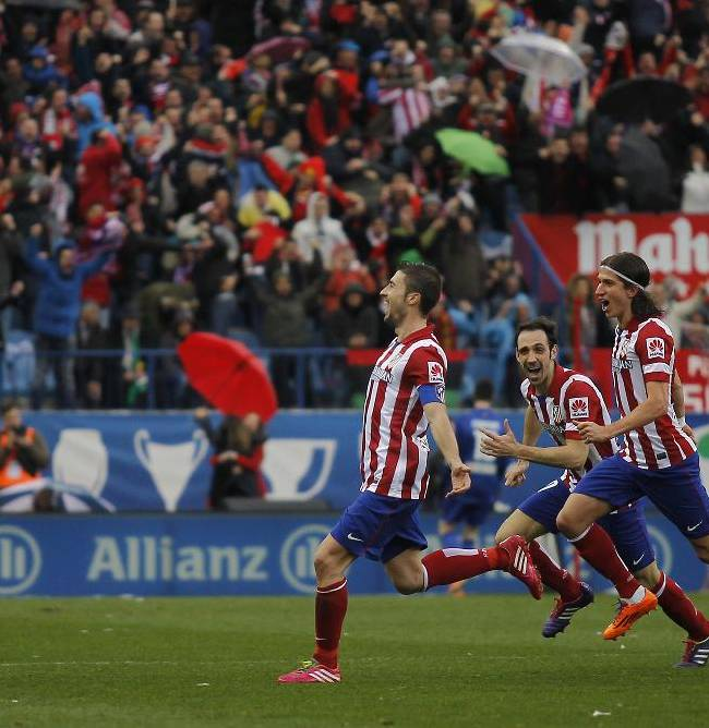 Atletico's Gabi , left, celebrates his goal during a Spanish La Liga soccer match between Atletico de Madrid and Real Madrid at the Vicente Calderon stadium in Madrid, Spain, Sunday, March 2, 2014