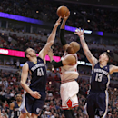Chicago Bulls' Taj Gibson, center, shoots over Memphis Grizzlies' Kosta Koufos (41) and Mike Miller during the second half of an NBA basketball game on Friday, March 7, 2014, in Chicago. The Grizzlies won 85-77 The Associated Press