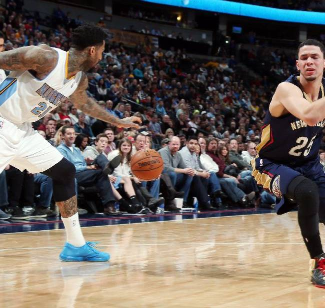New Orleans Pelicans guard Austin Rivers, right, reacts after losing the ball to Denver Nuggets forward Wilson Chandler in the fourth quarter of the Nuggets' 102-93 victory in an NBA basketball game in Denver on Sunday, Dec. 15, 2013
