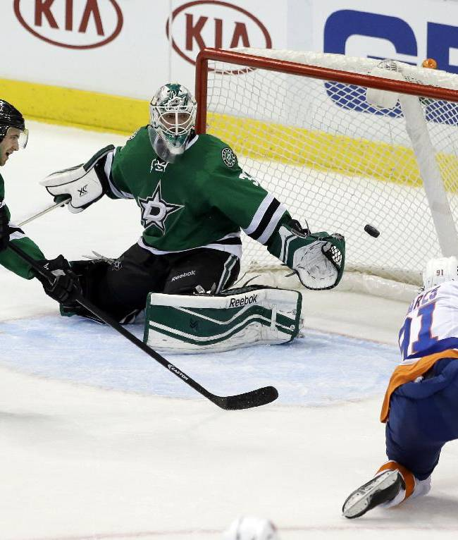 Dallas Stars' Alex Goligoski (33) watches as goalie Dan Ellis (30) is unable to stop a shot by New York Islanders center John Tavares (91) in the third period of an NHL hockey game, Sunday, Jan. 12, 2014, in Dallas. The Islanders scored three goals in the third helping them to the 4-2 win over the Stars