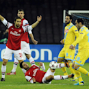 Arsenal's Arteta, center, goes for the ball as teammate Mathieu Flamini, left, Napolis' Goran Pandev, right, and Gonzalo Higuain, second right, wacth him, during a Champions League, group F, soccer match at the Naples San Paolo stadium, Italy, Wednesday,