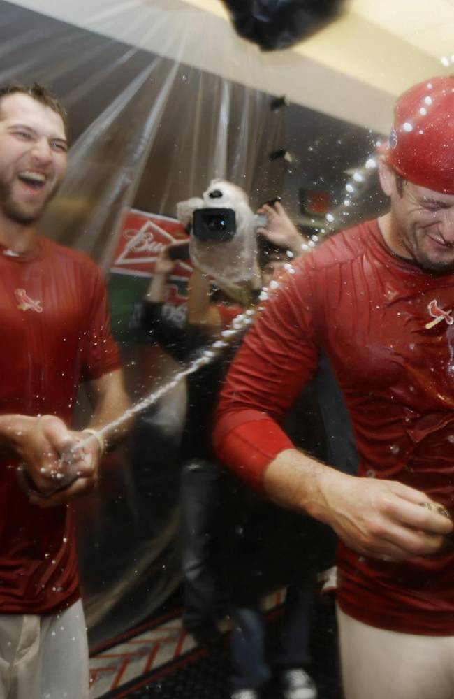 St. Louis Cardinals' Michael Wacha, left, sprays David Freese, right, after the Cardinals defeated the Pittsburgh Pirates 6-1 in Game 5 in a National League baseball division series, Wednesday, Oct. 9, 2013, in St. Louis. The Cardinals advanced to the NL championship series against the Los Angeles Dodgers