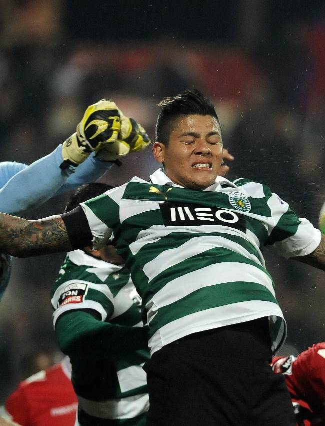 Sporting Lisbon's Marcos Rojo, right, vies for a high ball with Gil Vicente's goalkeeper Adriano Facchini in a Portuguese League soccer match at the Cidade de Barcelos stadium, Barcelos, northern Portugal, Sunday, Dec. 8, 2013