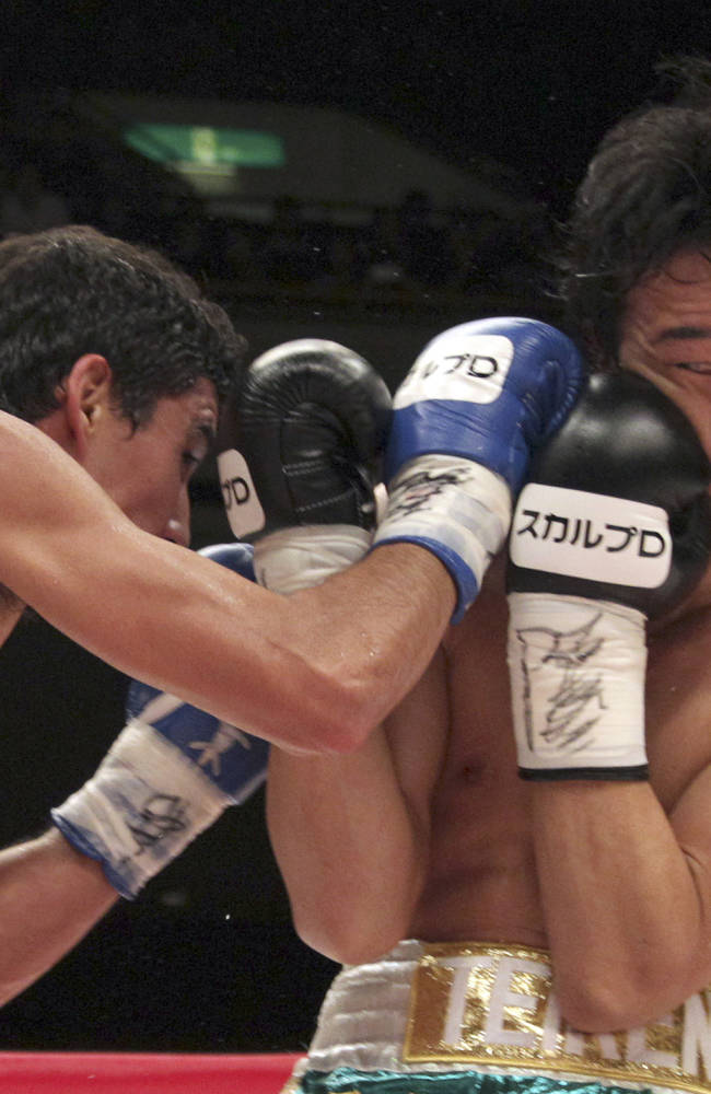 Japanese champion Shinsuke Yamanaka, right, blocks a punch from Mexican challenger Alberto Guevara in the fourth round of their WBC bantamweight title bout in Tokyo, Sunday, Nov. 10, 2013. Yamanaka knocked out Guevara in the ninth round to defend his title