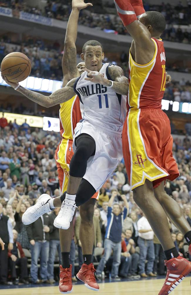Dallas Mavericks shooting guard Monta Ellis (11) passes off under the basket against Houston Rockets Dwight Howard (12)  and Terrence Jones during the final minute of an NBA basketball game in Dallas, Wednesday, Nov. 20, 2013. The Mavericks won 123-120