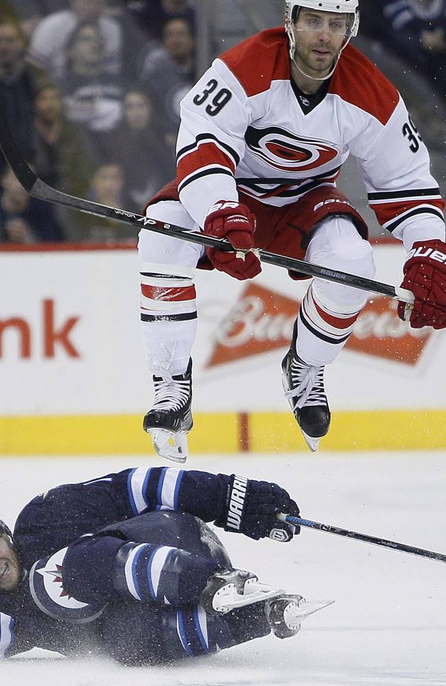 Carolina Hurricanes' Patrick Dwyer (39) leaps over Winnipeg Jets' Matt Halischuk (15) during the second period of an NHL hockey game, Saturday, March 22, 2014, in Winnipeg, Manitoba