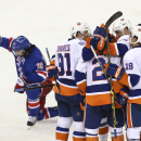 The New York Islanders celebrate a goal by Nick Leddy as New York Rangers right wing Mats Zuccarello (36) kneels beside them during the third period of an NHL hockey game at Madison Square Garden, Tuesday, Oct. 14, 2014, in New York. The Islanders won 6-3