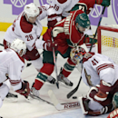Arizona Coyotes goalie Mike Smith, right, gets some help from Keith Yandle, left, and Michael Stone as Minnesota Wild right wing Justin Fontaine tries a wrap-around shot in the third period of an NHL hockey game, Thursday, Oct. 23, 2014, in St. Paul, Minn