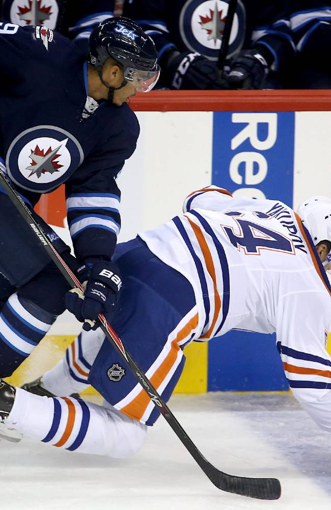 Winnipeg Jets' Evander Kane (9) takes down Edmonton Oilers' Nail Yakupov (64) during the first period of a preseason NHL hockey game in Winnipeg, Manitoba, Tuesday, Sept. 17, 2013
