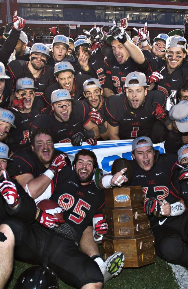 Laval players celebrate after defeating Montreal Carabins in the RSEQ final Dunsmore Cup football game Saturday, Nov. 9, 2013 in Quebec City