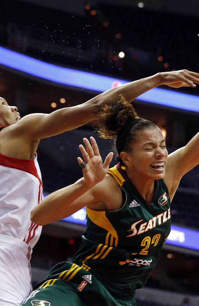 Washington Mystics forward Monique Currie (25) fouls Seattle Storm forward Alysha Clark (32) during the second half of a WNBA basketball game Saturday, May 24, 2014 in Washington.  The Storm won 73-65