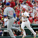 St. Louis Cardinals' Yadier Molina (4) runs home on a double by teammate Jhonny Peralta as Chicago Cubs' Blake Parker (50) looks for the ball in the eighth inning of a baseball game, Sunday, April 13, 2014, in St. Louis The Associated Press