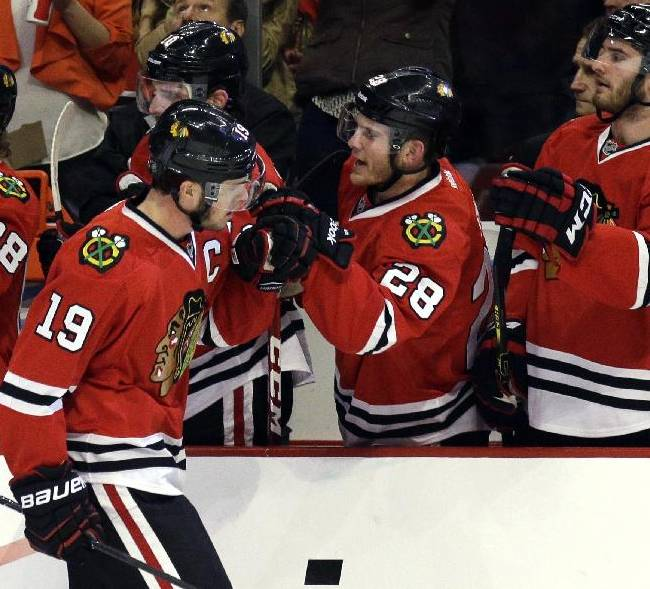 Chicago Blackhawks' Jonathan Toews (19) celebrates with teammates after scoring hi goal during the first period  in Game 2 of an NHL hockey second-round playoff series against the Minnesota Wild in Chicago, Sunday, May 4, 2014