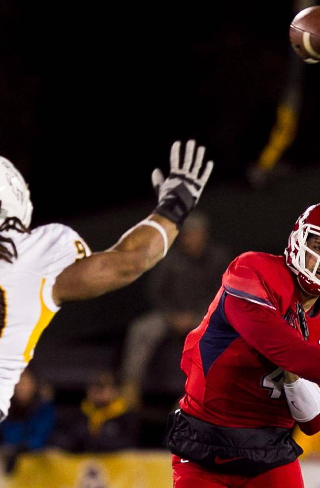Fresno State quarterback Derek Carr (4) throws a pass past Wyoming defensive end Uso Olive (90) Saturday Nov. 9, 2013 during the first half of the game at War Memorial Stadium in Laramie, Wyo