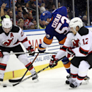 New Jersey Devils left wing Mike Cammalleri (23) and right wing Damien Brunner (12) battle for the puck with New York Islanders center Casey Cizikas (53) in the third period of an NHL hockey game at Nassau Coliseum on Saturday, Nov. 29, 2014, in Uniondale