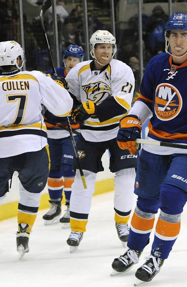 Nashville Predators' Matt Cullen (7) congratulates Nashville Predators' Patric Hornqvist (27) after Hornqvist scored a goal as New York Islanders' Brock Nelson (29) stakes past during the third period of an NHL hockey game on Tuesday, Nov. 12, 2013, in Uniondale, N.Y. The Islanders won 3-1