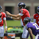 Baltimore Ravens quarterback Joe Flacco, center, prepares to catch a snapped ball as fellow quarterbacks Keith Wenning, back left, and Tyrod Taylor, as well as running back Ray Rice (27) look on during an NFL football training camp, Saturday, July 26, 201