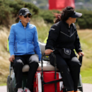 Michelle Wie of the US, left, is driven back to the clubhouse after play has been suspended due to the high winds during the third round of the Women's British Open golf championship on the Old Course at St Andrews, Scotland, Saturday Aug. 3, 2013. (AP Photo/Scott Heppell)