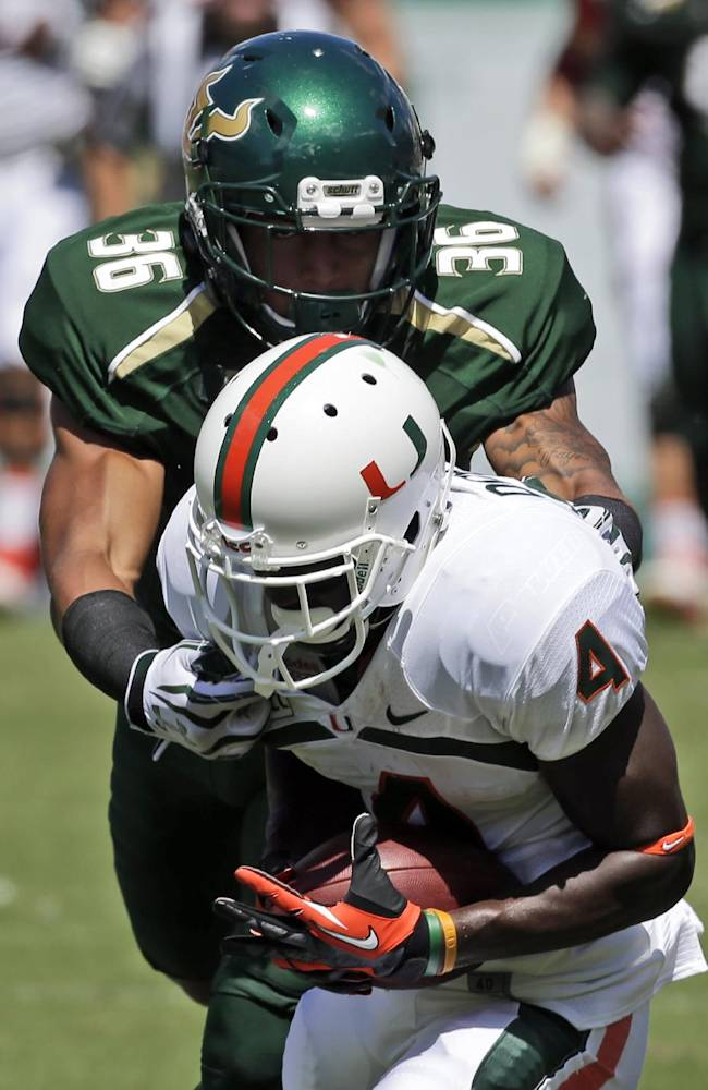 Miami wide receiver Phillip Dorsett (4) pulls in a pass in front of South Florida defensive back Nate Godwin (36) during the first quarter of an NCAA college football game Saturday, Sept. 28, 2013, in Tampa, Fla. Miami won the game 49-21