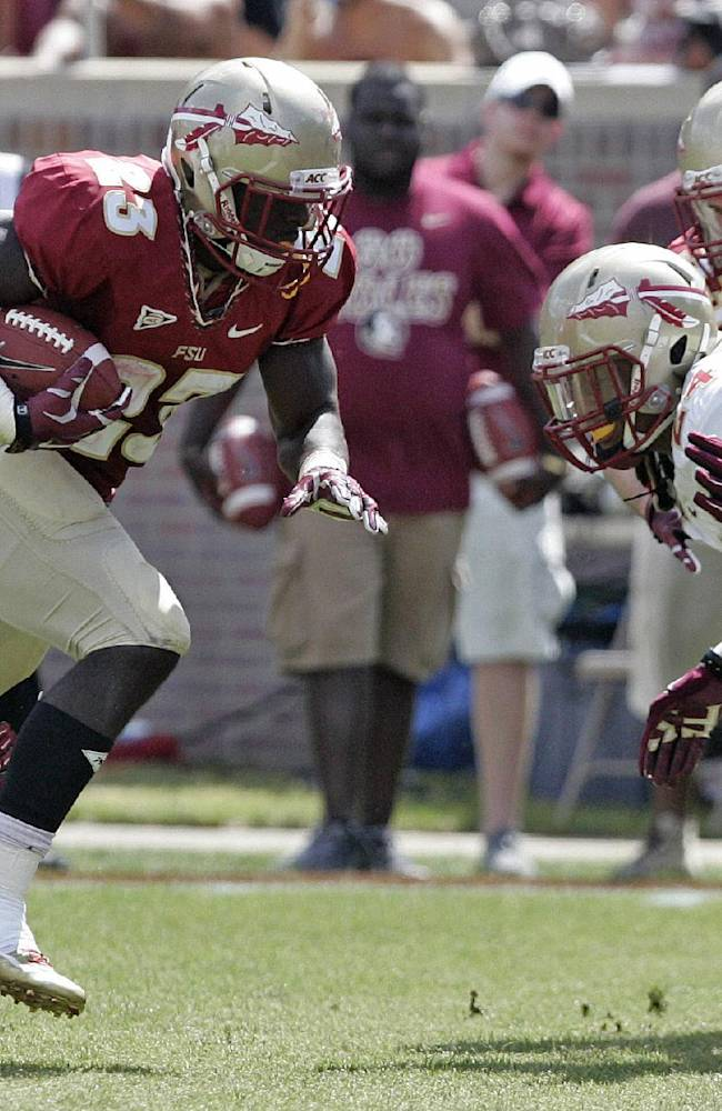 Florida State garnet running back Freddie Stevenson (23) slips the tackle of gold squad's Nick Waisome, left, and avoids Terrance Smith, right, as he scores a touchdown in the first half of an NCAA college spring football game on Saturday, April 12, 2014, in Tallahassee, Fla