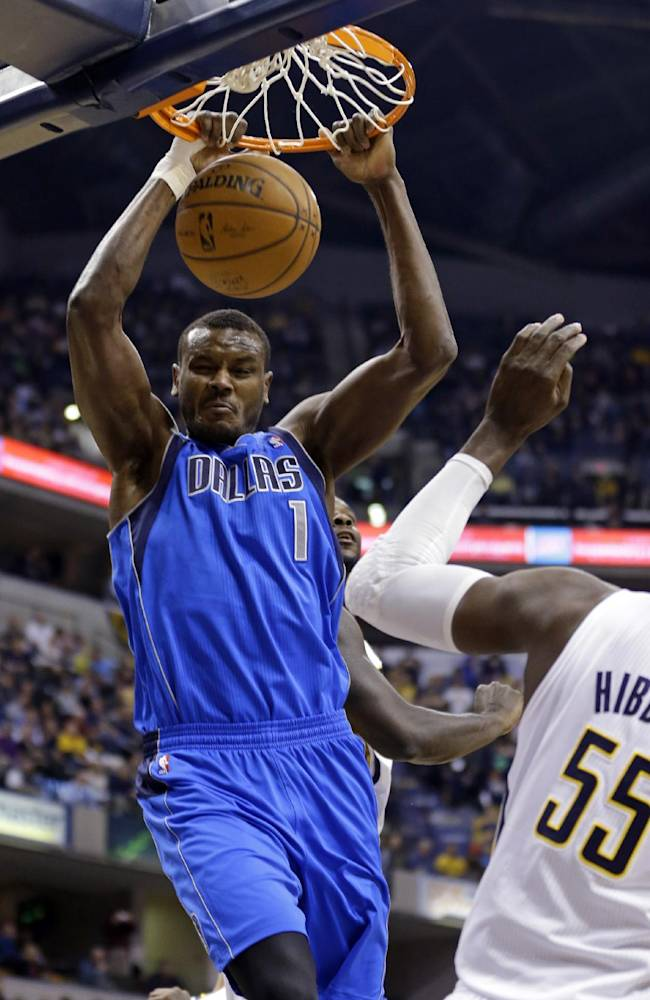 Dallas Mavericks center Samuel Dalembert, left, gets a dunk over Indiana Pacers center Roy Hibbert during the first half of an NBA basketball game in Indianapolis, Wednesday, Feb. 12, 2014